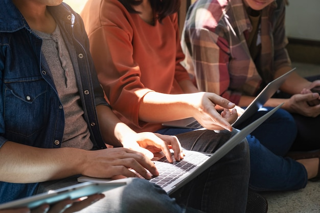 Groupe d'adolescents utilisant un ordinateur et une tablette pour apprendre en ligne.