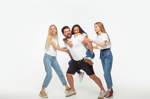 Groupe d'adorables amis multiethniques s'amusant isolé sur fond blanc studio