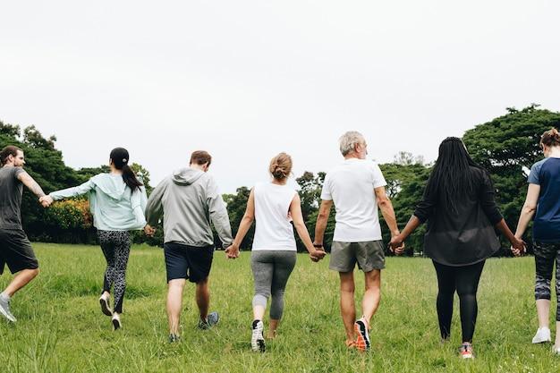 Groupe d'adultes se tenant la main dans le parc