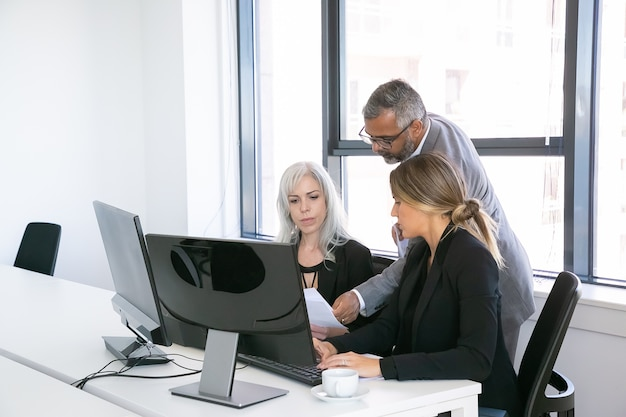 Groupe d'affaires sérieux de trois rapports d'analyse, assis sur le lieu de travail avec des moniteurs ensemble, tenant, examinant et discutant des documents. copiez l'espace. concept de réunion d'affaires