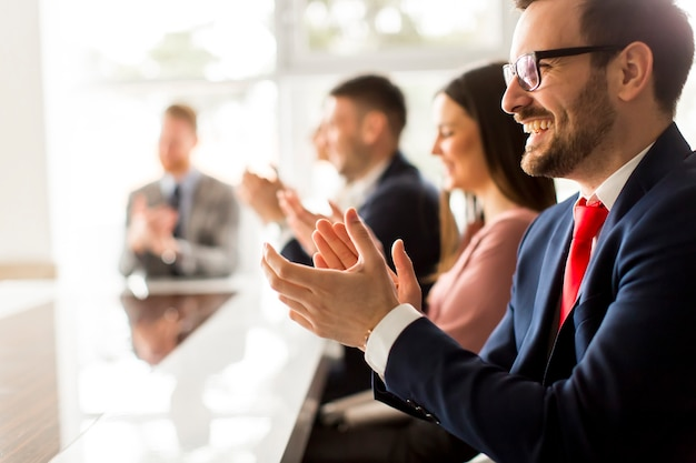 Groupe d'affaires souriant frappant des mains à la réunion