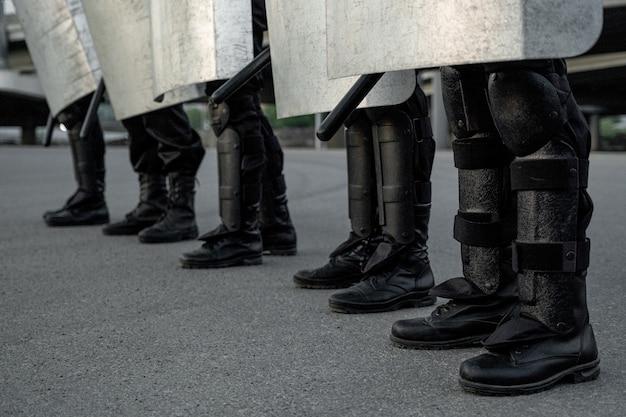 Groupe d'agents de la police anti-émeute en bottes noires debout sur l'asphalte dans la rue et tenant des boucliers