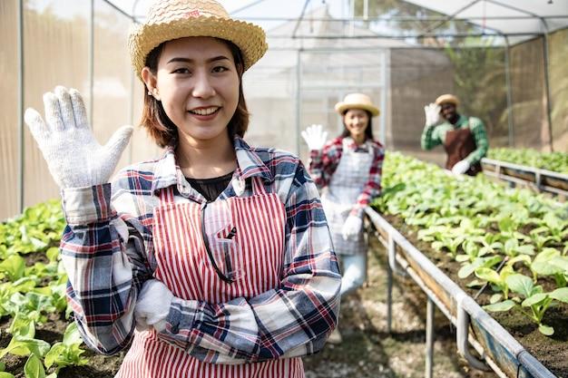 Groupe d'agriculteurs agitant hans pour le client à la ferme biologique