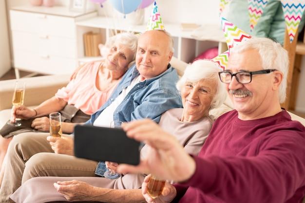 Groupe d'aînés joyeux faisant selfie sur canapé alors qu'ils étaient réunis pour une fête d'anniversaire à la maison