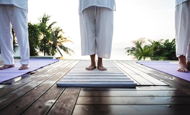 Groupe d'aînés pratiquant le yoga au bord de la piscine