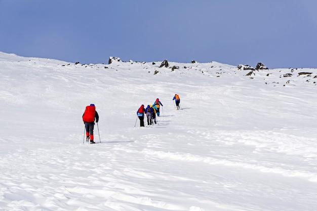 Groupe d'alpinistes dans le paysage arctique montagneux sous un ciel bleu lumineux