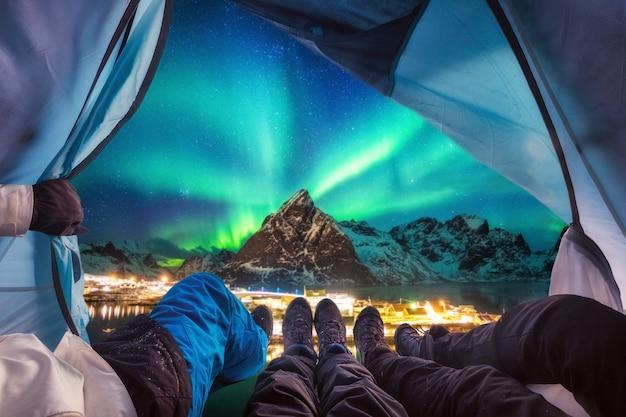 Un groupe d'alpinistes est à l'intérieur du camping avec des aurores boréales au-dessus de la montagne au village de sakrisoy