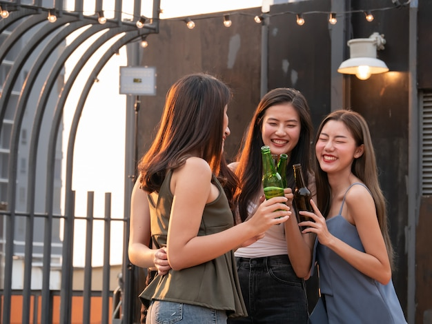 Groupe d'ami asiatique acclamant et buvant à la fête en terrasse. jeunes profitant et traîner sur le toit au coucher du soleil