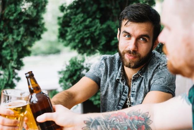Groupe d'amis acclamant des boissons alcoolisées à l'extérieur