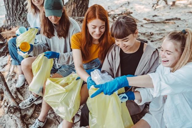 Groupe d'amis activistes ramassant des déchets plastiques dans le parc. conservation de l'environnement.