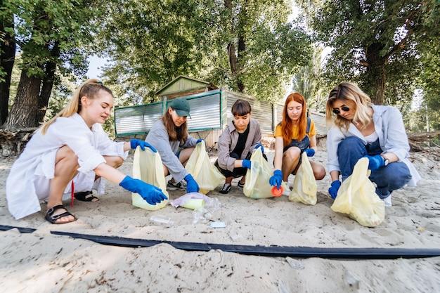 Groupe d'amis activistes ramassant des déchets plastiques sur la plage. protection de l'environnement.