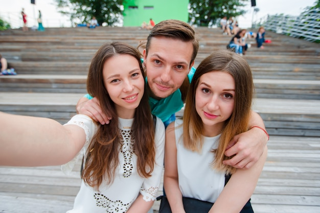 Groupe d'amis de l'adolescence heureux en riant et prenant un selfie dans la rue. trois amis en regardant prendre des photos avec tablette dans le parc