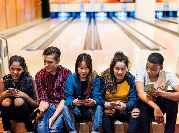 Groupe d'amis adolescents à l'aide de smartphone dans une piste de bowling