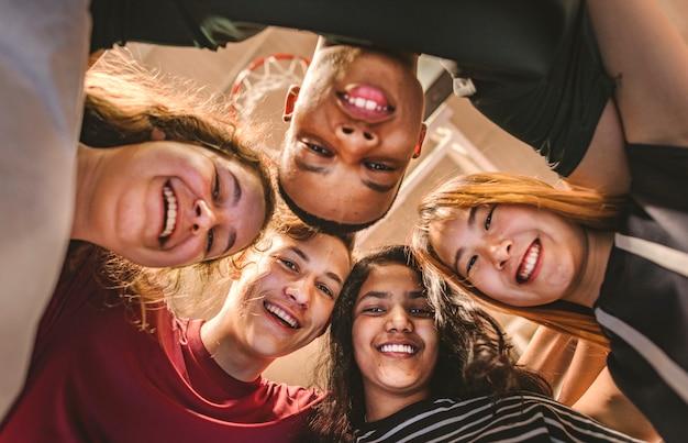 Groupe d'amis adolescents sur un concept de travail d'équipe et de convivialité de terrain de basket