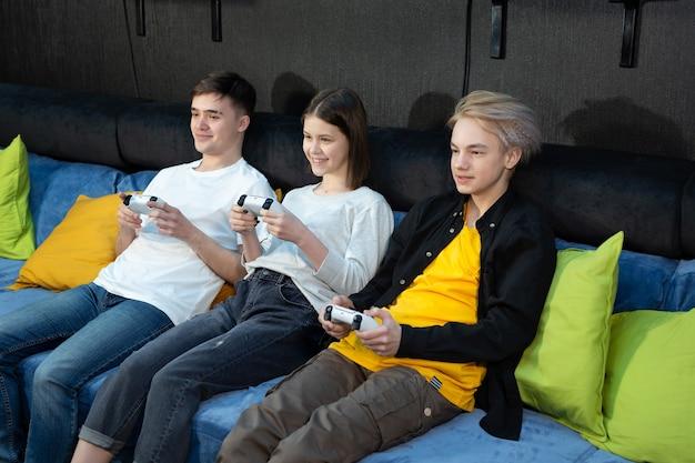 Groupe d'amis d'adolescents, de garçons et de filles jouant à des jeux vidéo sur une console dans un club de jeux.