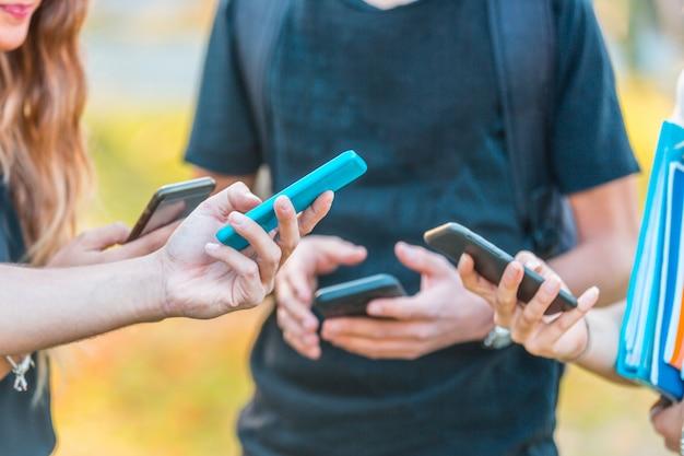 Groupe d'amis adolescents avec smartphones au parc