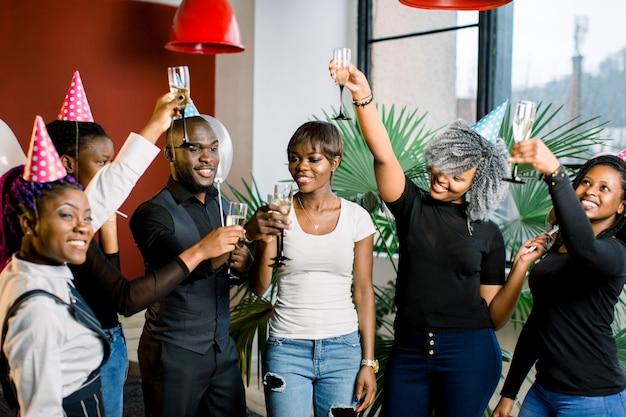 Groupe d'amis africains heureux buvant du champagne et célébrant la fête d'anniversaire