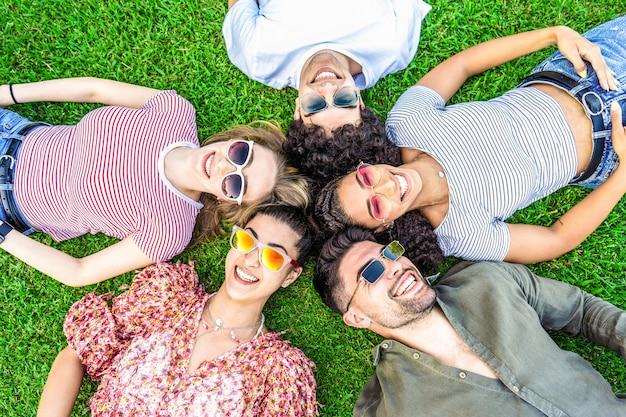 Groupe d'amis allongé sur la prairie du parc portant des lunettes de soleil tendance colorées