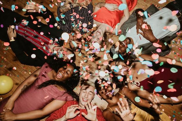 Groupe d'amis allongés sur le sol lors d'une fête