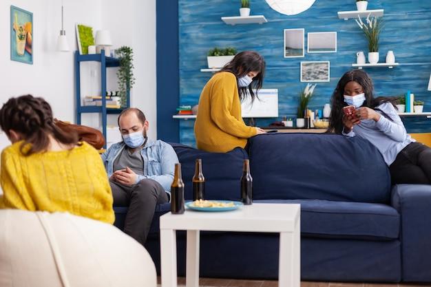 Groupe d'amis antisociaux multiethniques gardant une distance sociale en naviguant sur des smartphones dans le salon de l'appartement pendant la pandémie mondiale de coronavirus.