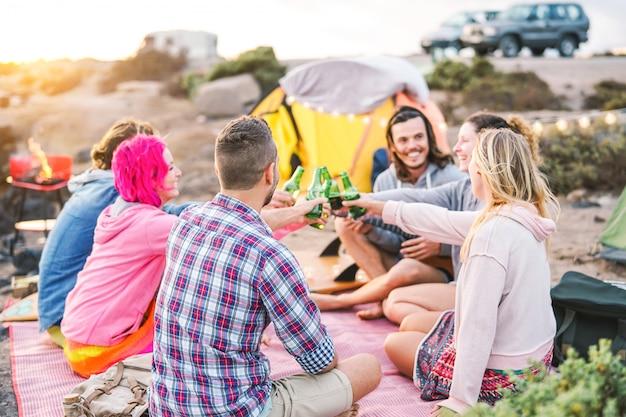 Groupe d'amis applaudir avec des bières au dîner barbecue sur la plage