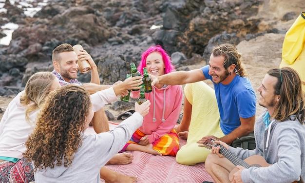 Groupe d'amis applaudir avec des bières sur la plage