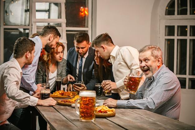 Groupe d'amis appréciant des boissons en soirée avec de la bière sur une table en bois