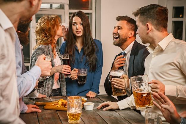 Groupe D'amis Appréciant Des Boissons En Soirée Avec De La Bière Sur Une Table En Bois Photo gratuit
