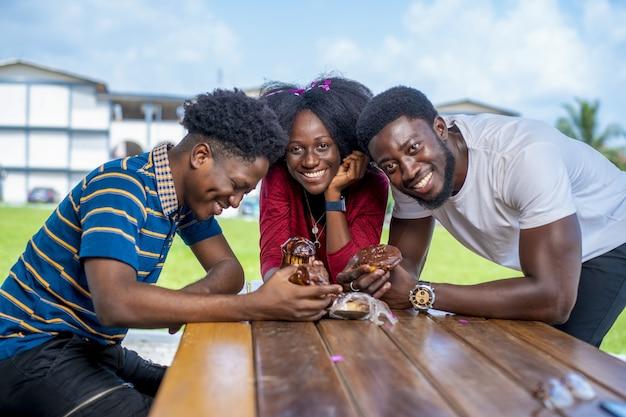 Groupe d'amis appréciant le dessert dans un parc pendant la journée