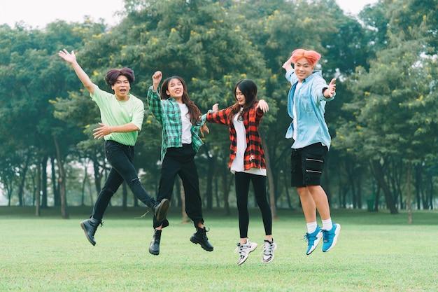 Un groupe d'amis asiatiques heureux a sauté ensemble sur l'herbe dans le parc