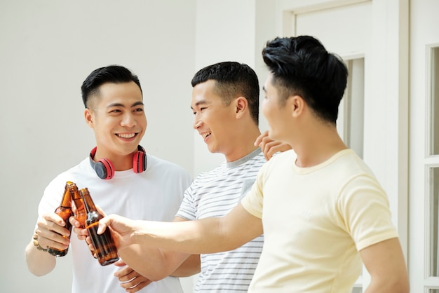 Groupe d'amis asiatiques portant un toast avec des bouteilles de bière lors de leur réunion