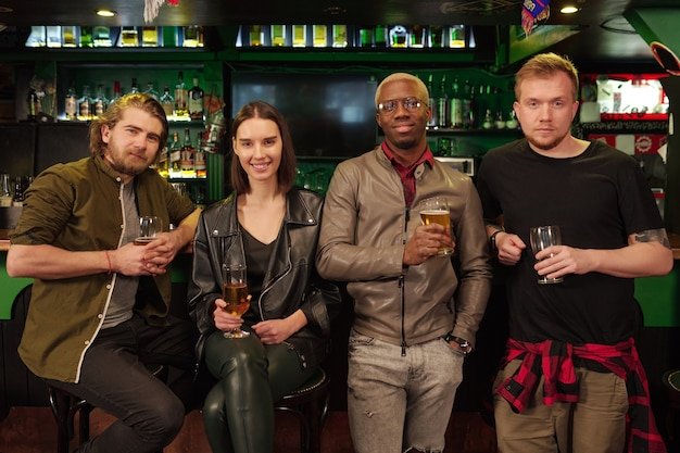 Groupe d'amis assis au comptoir du bar avec de la bière et souriant à la caméra dans le pub