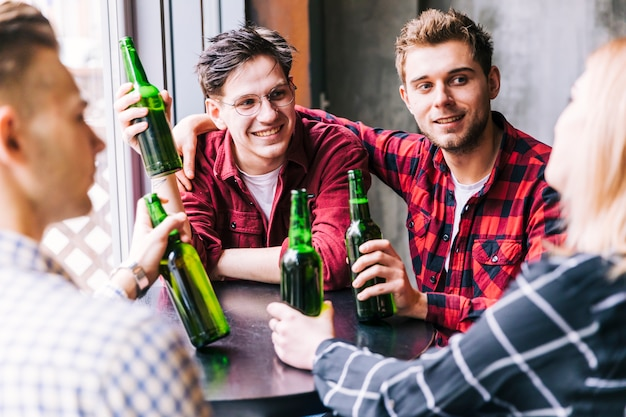 Groupe d'amis assis autour de la table en dégustant une boisson au restaurant du pub