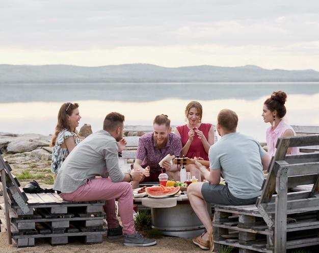Groupe d'amis assis autour d'une table près du lac pittoresque le soir d'été, bavardant, mangeant et profitant de leur temps ensemble
