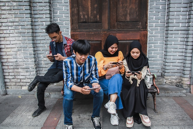 Groupe d'amis assis sur un banc et jouer à des jeux en ligne sur téléphone intelligent
