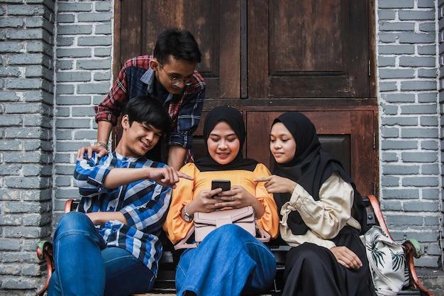 Groupe d'amis assis sur un banc et regarder la vidéo sur un téléphone intelligent ensemble