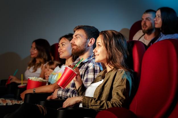 Groupe d'amis assis dans une salle de cinéma avec pop-corn et boissons