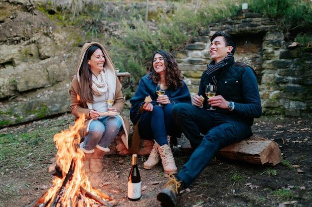 Groupe d'amis assis devant un feu de joie, boire un verre de vin tout en parlant et en riant. ensemble, concept d'amitié.