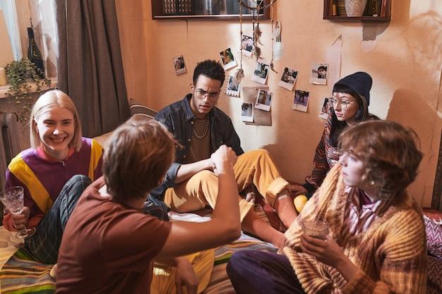 Groupe d'amis assis par terre buvant des boissons alcoolisées et se parlant pendant une fête domestique à la maison