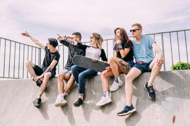 Groupe d'amis assis sur une rampe pointant vers quelque chose