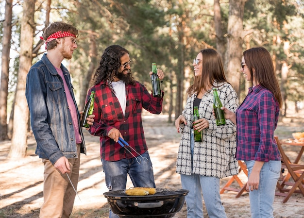 Groupe d'amis ayant un barbecue avec des bières