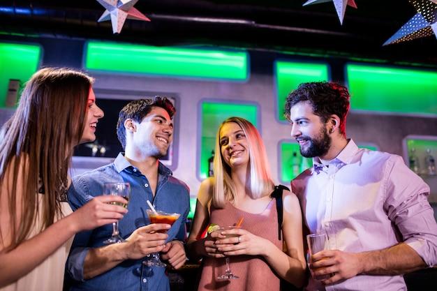 Groupe d'amis ayant un cocktail et du vin