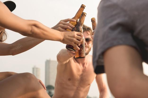 Groupe d'amis ayant une fête claging bouteilles de bière à la plage
