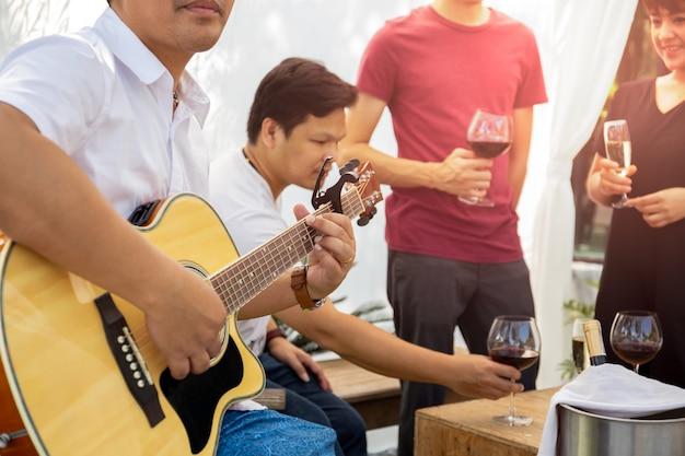 Groupe d'amis ayant une fête avec du vin rouge et jouant de la guitare en plein air.