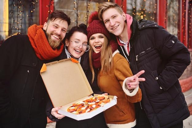 Groupe d'amis avec une boîte de pizza souriant et mangeant une pizza dans la rue