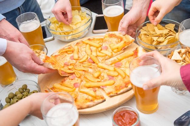 Groupe d'amis boivent de la bière, mangent de la pizza, parlent et sourient tout en se reposant à la maison