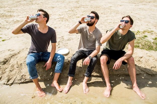 Groupe d'amis buvant de la bière sur la plage