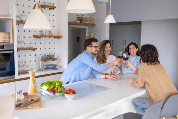 Groupe d'amis buvant du vin dans la cuisine