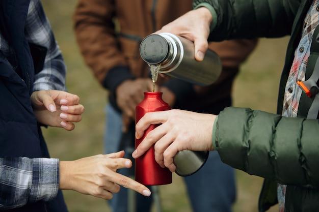 Groupe d'amis en camping ou en randonnée en journée d'automne. hommes et femmes avec des sacs à dos touristiques dans la forêt, parlant, riant. activité de loisirs, amitié, week-end. buvez du thé ou du café.