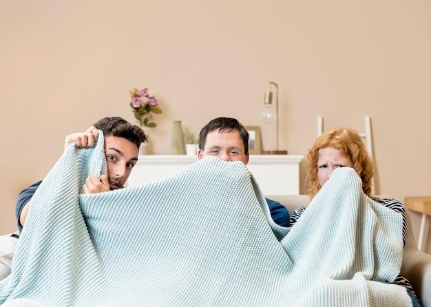 Groupe d'amis sur canapé avec couverture
